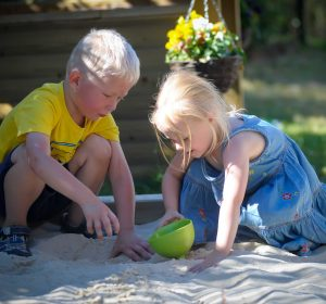 Two children playing in the sandpit