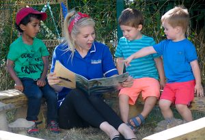 Reading a book with three children in the garden